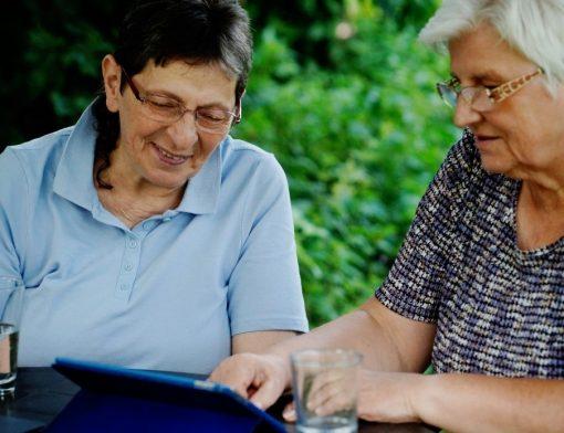 Duas idosas sentadas à mesa visualizando algo em um tablet - revisão do benefício